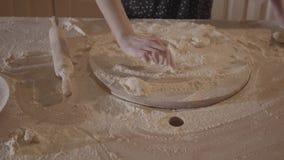 Mujer desconocida en armadura del drenaje de la tabla de cocina en el tablero con la harina y el polvo blanco entonces que sopla almacen de metraje de vídeo