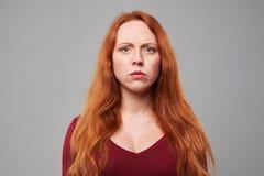 Mujer descontenta con el pelo rojo sobre fondo gris Imagen de archivo