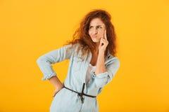 Mujer descontentada confusa 20s que piensa y que mira a un lado, isolat foto de archivo