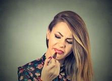 Mujer descontentada que aplica el lápiz labial Imagen de archivo