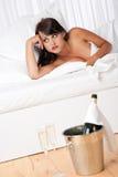 Mujer descubierta atractiva en la cama blanca con champán Fotografía de archivo libre de regalías