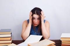 Mujer desesperada cansada joven del estudiante que se sienta en la tabla con el te Imagen de archivo