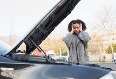 Mujer desesperada después de comprobar el motor roto coche fotos de archivo