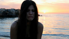 Mujer desesperada que llora durante puesta del sol en la playa metrajes