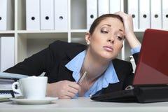 Mujer desmotivada en su escritorio Foto de archivo libre de regalías
