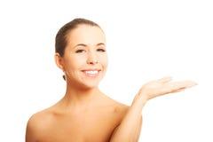 Mujer desnuda con la mano abierta que muestra el espacio Imágenes de archivo libres de regalías