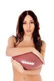 Mujer desnuda hermosa que sostiene la bola del fútbol americano Fotos de archivo