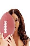 Mujer desnuda hermosa que sostiene la bola del fútbol americano Imagen de archivo libre de regalías