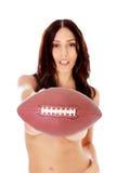 Mujer desnuda hermosa que sostiene la bola del fútbol americano Foto de archivo