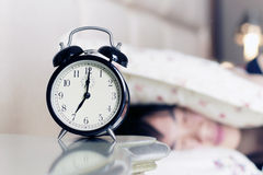 Mujer despertada por el ruido del reloj de alarma Imagen de archivo