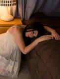 Mujer despierta al lado de cama Fotos de archivo