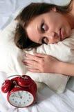 Mujer despierta con el reloj de alarma Imagen de archivo libre de regalías