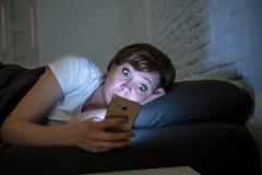 Mujer despierta preocupante hermosa joven que miente en cama usando el teléfono elegante tarde en la noche en un dormitorio oscur imágenes de archivo libres de regalías