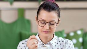 Mujer despreocupada casual del primer en vidrios que come el yogur natural de la lechería que tiene emoción positiva metrajes