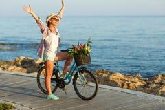 Mujer despreocupada con el montar a caballo de la bicicleta en una trayectoria de madera en el mar, Foto de archivo libre de regalías