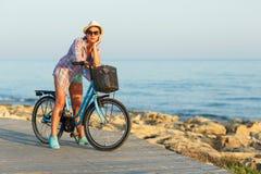 Mujer despreocupada con el montar a caballo de la bicicleta en una trayectoria de madera en el mar Imágenes de archivo libres de regalías