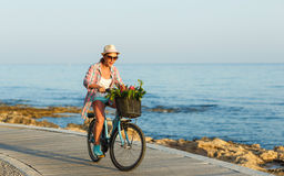 Mujer despreocupada con el montar a caballo de la bicicleta en una trayectoria de madera en el mar, Imagen de archivo libre de regalías