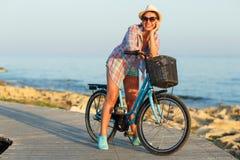 Mujer despreocupada con el montar a caballo de la bicicleta en una trayectoria de madera en el mar Fotos de archivo libres de regalías