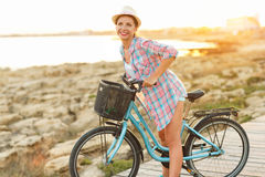 Mujer despreocupada con el montar a caballo de la bicicleta en una trayectoria de madera en el mar, Fotos de archivo libres de regalías
