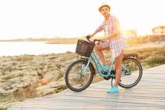 Mujer despreocupada con el montar a caballo de la bicicleta en una trayectoria de madera en el mar, Imágenes de archivo libres de regalías
