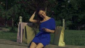 Mujer despreocupada del comprador que usa el teléfono elegante en la ciudad almacen de metraje de vídeo