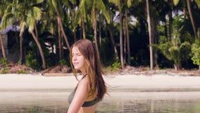 Mujer despreocupada en el traje de baño que corre en el agua en la playa del mar Mujer sonriente que goza de la agua de mar en la almacen de metraje de vídeo