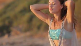 Mujer despreocupada en puesta del sol en la playa de la isla.