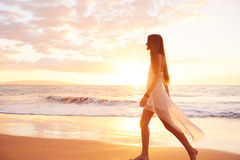 Mujer despreocupada feliz en la playa en la puesta del sol Imagen de archivo libre de regalías