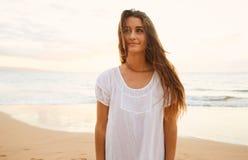 Mujer despreocupada feliz en la playa en la puesta del sol Fotos de archivo