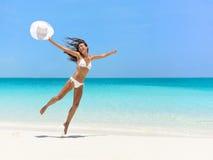Mujer despreocupada que salta en la playa durante verano Imagen de archivo