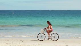 Mujer despreocupada que va en un paseo de la bici en la playa almacen de video