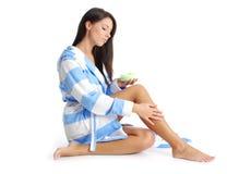Mujer después de la ducha que aplica la crema Fotografía de archivo libre de regalías