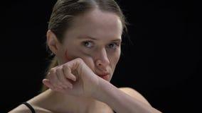 Mujer determinada que limpia la palabra fea escrita en cara, opinión social que lucha almacen de metraje de vídeo