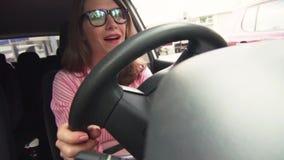 Mujer detrás de la rueda de los miedos de las demostraciones de un coche almacen de metraje de vídeo