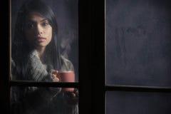 Mujer detrás de la ventana con una taza de café Fotografía de archivo