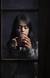 Mujer detrás de la ventana con una taza de café o de té Foto de archivo libre de regalías