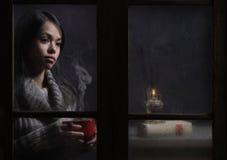 Mujer detrás de la ventana mojada Foto de archivo libre de regalías