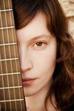 Mujer detrás del fretboard de la guitarra Imagen de archivo