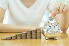 Mujer dinero-joven de ahorro que pone una moneda en una dinero-caja Foto de archivo libre de regalías