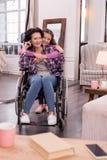 Mujer discapacitada de abarcamiento de la muchacha alegre Foto de archivo libre de regalías