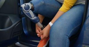 Mujer discapacitada hermosa que ata el cordón de zapato en el coche 4k almacen de metraje de vídeo