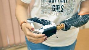 Mujer discapacitada joven con el brazo prostético que lo prueba por primera vez 4K almacen de metraje de vídeo