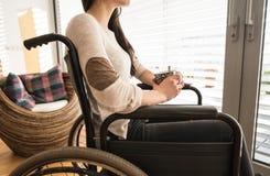 Mujer discapacitada joven irreconocible en silla de ruedas en casa imagenes de archivo