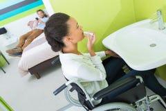 Mujer discapacitada que pone en maquillaje en la habitación Imagenes de archivo
