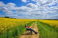 Mujer discapacitada que toma el sol en una silla de ruedas, campo de la violación, primavera Foto de archivo