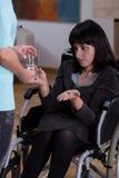 Mujer discapacitada que toma medicinas Imagen de archivo libre de regalías