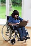 Mujer discapacitada que usa el ordenador portátil Imágenes de archivo libres de regalías