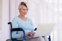 Mujer discapacitada que usa el ordenador portátil Foto de archivo libre de regalías