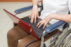 Mujer discapacitada que usa un ordenador portátil en su silla de ruedas Imagen de archivo