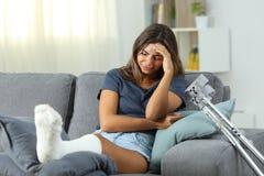 Mujer discapacitada triste que se queja solamente en casa imagenes de archivo
